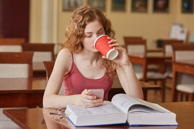 Image of pensive intelligent sweet curly haired girl, holding papercup of drink in one hand, drinking coffee, using her smartphone, reading news, having opened book on desk. studying concept.