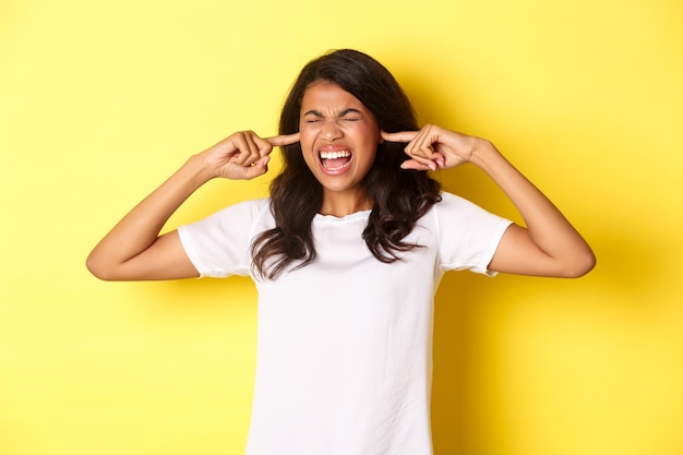 Image of pissed-off african-american girl, cant stand loud bothering noise, shut ears and screaming annoyed, standing over yellow background.