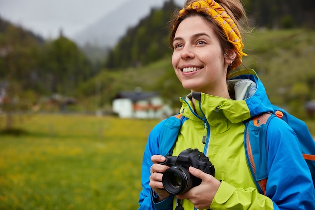 Image of pleasant looking cheerful woman dressed casually, holds professional camera