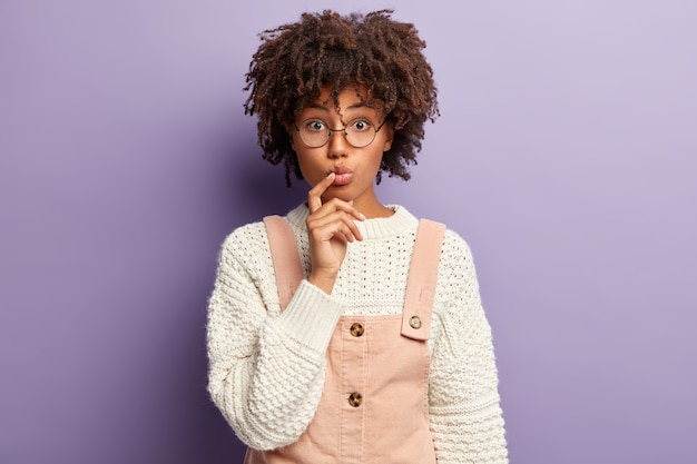 Image of pleasant looking young woman has folded lips, curly hair, keeps finger near mouth, listens attentively news, wears fashionable outfit, round spectacles, poses against purple wall