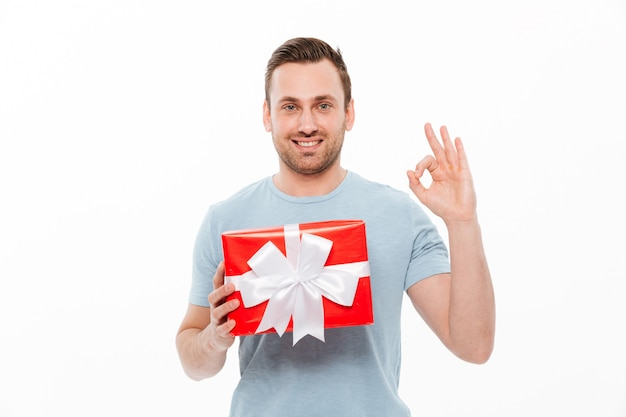 Image of pleased brunette guy smiling and showing ok sign while holding red present box with bow
