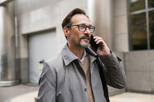 Image of pleased businessman in eyeglasses talking on cellphone while standing near office building at city street