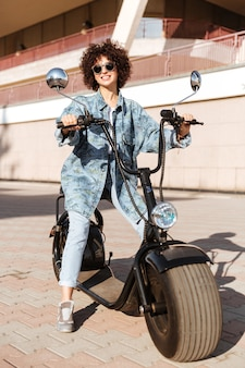 Image of pleased curly woman in sunglasses sitting on modern motorbike outdoors