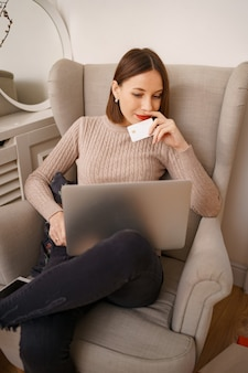Image of pleased nice woman holding credit card with copy space using laptop