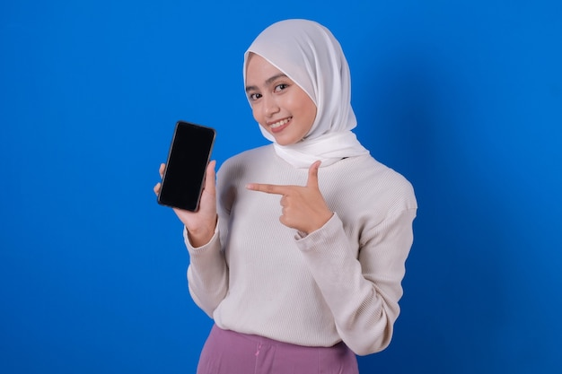 Image of pointing young muslim woman with her mobile phone