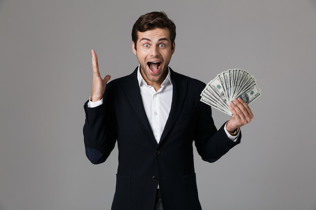 Image of positive businessman 30s in suit smiling and holding fan of money in dollar banknotes, isolated over gray wall