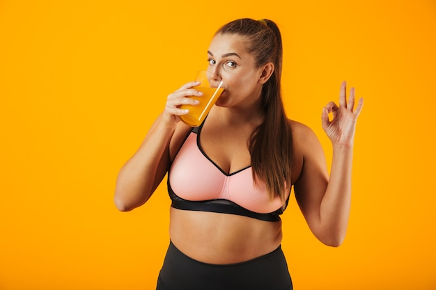 Image of pretty chubby woman in tracksuit smiling and drinking orange juice, isolated over yellow background