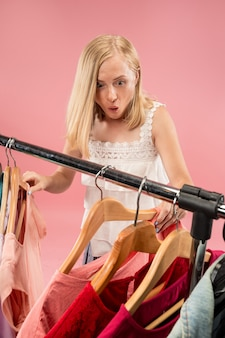 Image of pretty female looking a dress while choosing it.