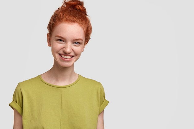 Image of pretty red haired girl has charming smile on face, wears casual green t shirt, feels happy, isolated over white wall with free space for your advertising content or promotion. emotions