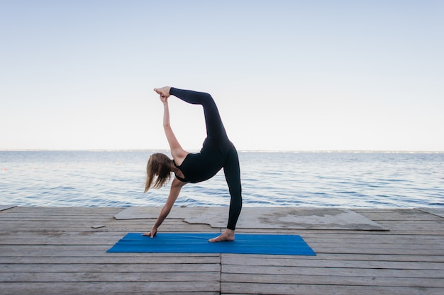 Image of a pretty woman doing yoga at the lake