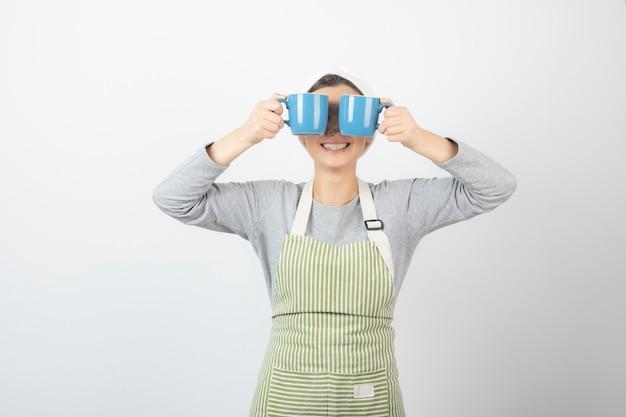 Immagine di una bella giovane donna in grembiule che copre gli occhi con due tazze blu