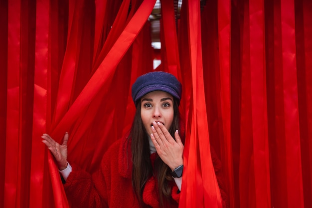 Image of a pretty young woman looks out between red curtain.