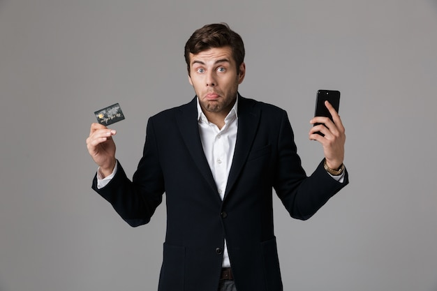 Image of puzzled businessman 30s in suit holding credit card and cell phone, isolated over gray wall