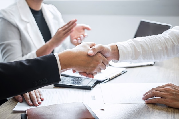 Image of recruiter in suit and new employee shaking hands and clap after good deal interviewing
