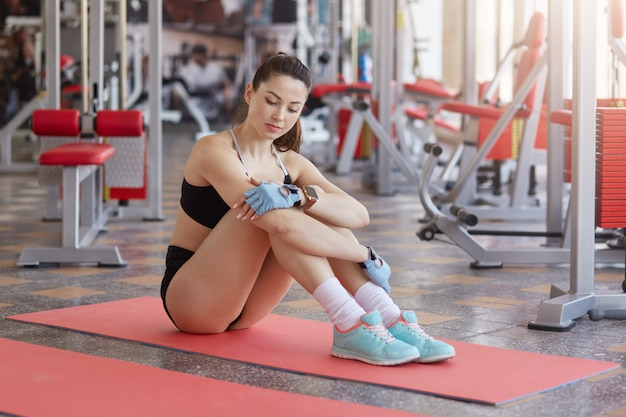 Image of relaxed fitness woman with perfect figure sits on exercise mat