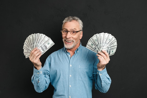 Image of rich happy adult man 60s with gray hair holding money two fans of 100 dollar bills and rejoicing his wealth, isolated over black wall