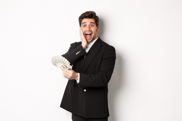 Immagine di un uomo ricco e felice in abito nero, che vince un premio, tiene in mano soldi e guarda eccitato alla telecamera, in piedi su sfondo bianco.
