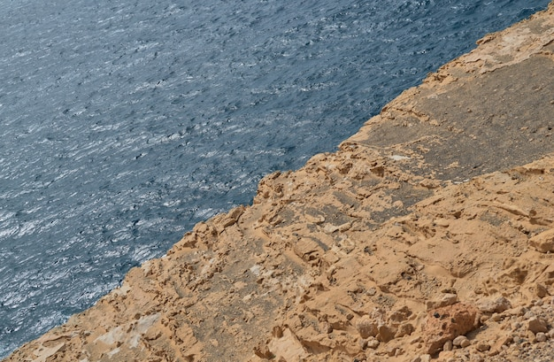 Image of rocky limestone formation in the middle and the blue sea in the other half in ajuy, fuerteventura, canary islands, spain