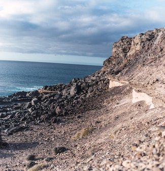 Image of a rocky slope along a sea coast under cloudy skies