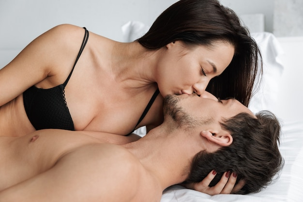 Image of romantic couple kissing together, while lying in bed at home or hotel apartment