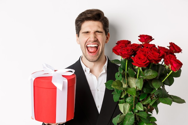 Image of sad guy in suit, got rejected and crying, holding bouquet of roses and present, standing miserable against white background