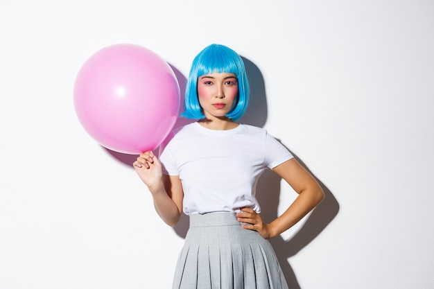 Image of sassy asian woman in blue wig, looking determined, holding pink balloon, standing.