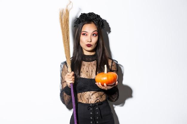 Immagine della strega impertinente in abito di pizzo gotico, tenendo in mano scopa e zucca, guardando nell'angolo in alto a sinistra con la bandiera di halloween, sfondo bianco.