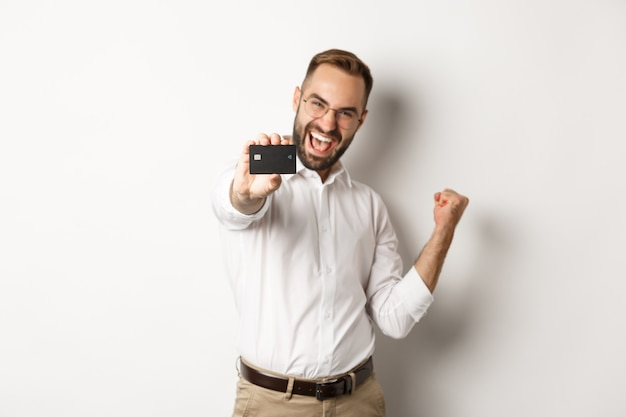 Immagine di uomo d'affari soddisfatto che mostra la carta di credito, facendo pompa pugno in rallegrarsi, in piedi