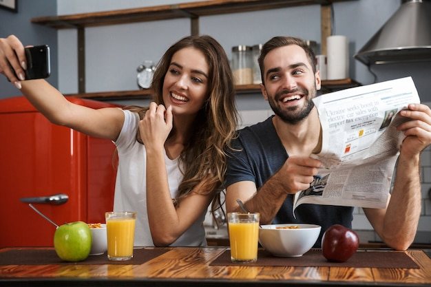 Image of satisfied couple man and woman taking selfie photo on cell phone while having breakfast in kitchen at home