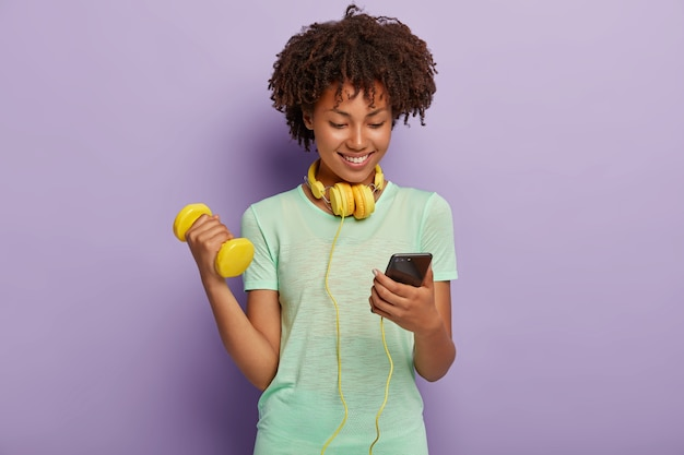 Image of satisfied dark haired curly fit girl chooses track in playlist, listens music via headphones, raises arm with dumbbell, has active training, isolated on violet wall. bodybuilding concept