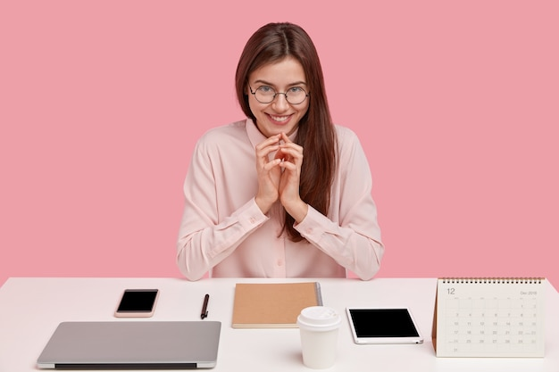 Image of satisfied european lady office worker being real perfectionist, keeps hands together, smiles gently