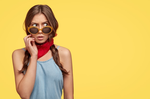Image of scared european woman with straight hair, wears trendy sunglasses, red banada around neck, looks with gloomy expression aside, shows free space against yellow wall for your text