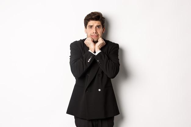 Immagine di un giovane uomo d'affari spaventato e insicuro in tuta, tremante di paura e con l'aria inorridita, in piedi su sfondo bianco