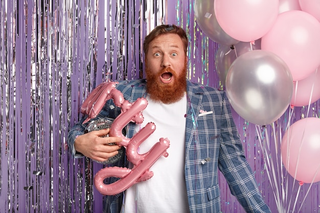 Image of scared red haired man carries shining disco ball, balloons, celebrates promotion in night club with colleagues, shocked with bad music, wears stylish checkered coat, isolated on purple wall