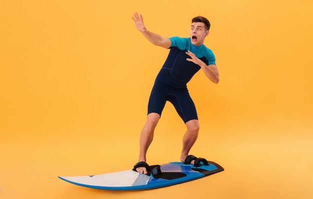 Image of scared screaming surfer in wetsuit using surfboard like on wave