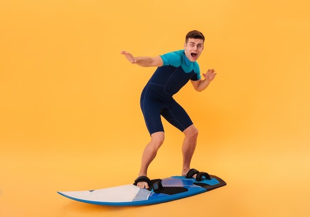 Image of scared surfer in wetsuit using surfboard like on wave and screaming