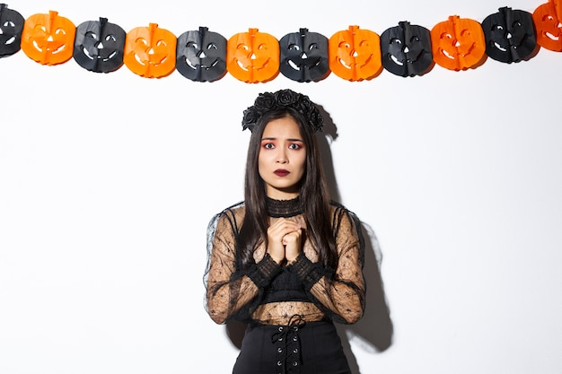 Image of scared and worried asian woman in witch costume looking concerned, wearing witch costume and standing against pumpkin banners.