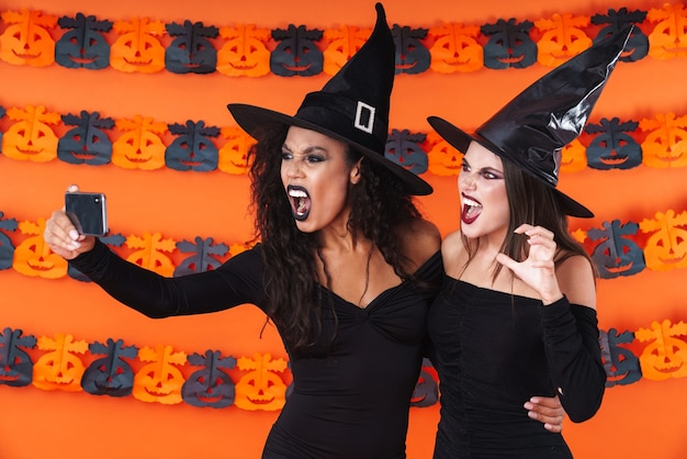 Image of scary witch women in black halloween costume taking selfie photo on cellphone with showing teeth isolated on orange pumpkin wall