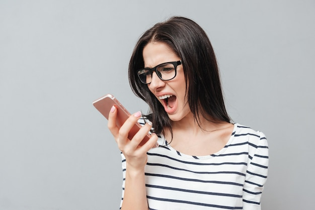 Image of screaming angry young woman wearing eyeglasses using phone over grey surface. look at phone.
