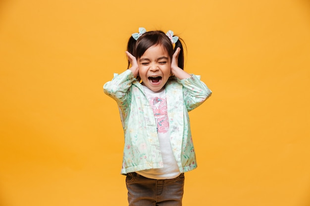 Image of screaming emotional little girl child standing isolated over yellow background.