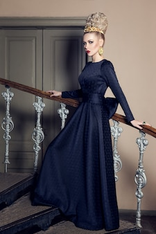 Image of a sensual woman in  black dress and accessories with evening makeup, posing on stairs