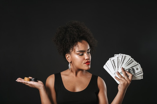 Image of a serious african woman posing isolated over black wall holding money and chips.