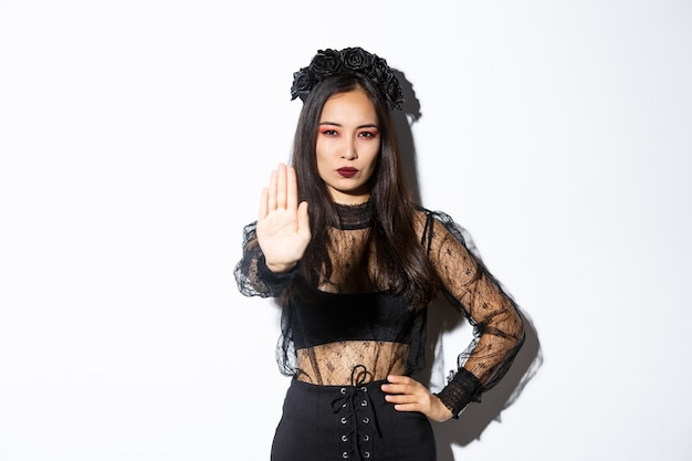 Image of serious asian woman in halloween costume of witch, showing stop gesture, forbid or prohibit something with displeased confident face, standing white background.