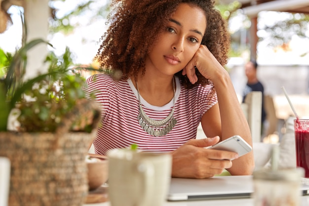 Image of serious black ethnic woman reads incoming message on mobile phone, checks email on cellular, sits at cafe interior with mug of coffee, connected to wireless internet, makes shopping