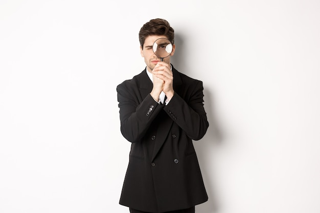 Image of serious businessman in black trendy suit, looking through magnifying glass, looking for employees, standing against white background