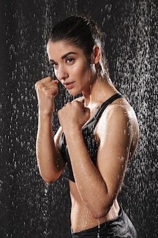 Image of serious caucasian sportive woman boxing and standing in defense position under rain drops, isolated over black background