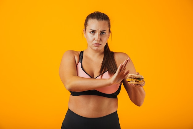 Image of serious chubby woman in tracksuit doing stop gesture while holding sandwich, isolated over yellow background