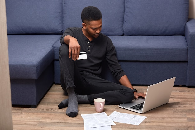 Image of serious pensive afroamerican man staying at home, being confused with online services, holding credit card