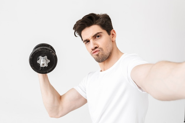 Image of serious young man posing isolated over white wall holding dumbbell make exercise take a selfie by camera.
