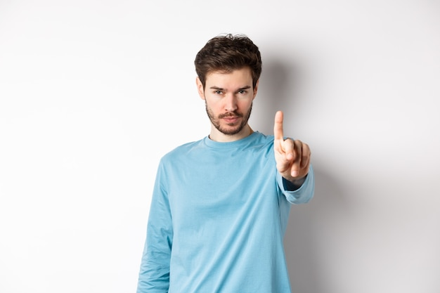 Image of serious young man with beard, shaking finger in disapproval, prohibit or forbid something, standing over white background and saying no
